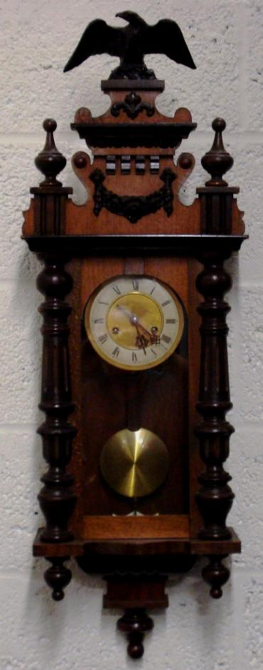 German 8 day gong striking wall clock circa 1900, spring driven pendulum movement housed in an oak and pine case with decorative turned finials and side columns together with applied swags and surmounted by an eagle. Ivory and brass coloured dial with black roman hour markers and black steel hands, and an enamel pendulum regulation plate at the case bottom.
