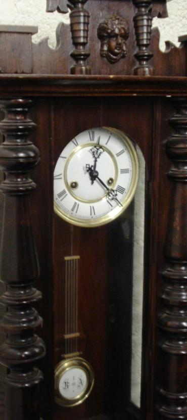 German 8 day gong striking regulator style wall clock circa 1900, with a spring driven pendulum movement housed in a dark pine case with decorative turned finials and side columns together with an applied mask decoration. White enamel and gilded brass dial with black roman hour markers and ornate black steel hands, and a grid iron style pendulum.