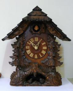 "New quartz mantel / wall cuckoo clock by Harzer. Pine wood case with stylised pine tree decoration and nesting bird motif. Traditional carved light coloured wood chapter ring with roman hours and matching wooden hands. Visible pendulum and carved light wood cuckoo bird display on the hour.  Dimensions: Height - 16.5"", width - 13.5"", depth - 10""."