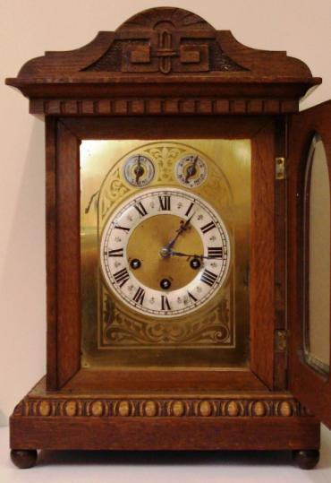 German oak cased 8 day Westminster chime bracket clock by Junghans circa 1900. Architectural case with carved decorated top and plinth, with wooden ball feet. Carved wooden door with heavily chamfered glass over acid etched brass dial plate with Chime / Silent and Slow / Fast controls at the top. White silvered chapter ring with black roman hours and ornate blued steel hands. Square brass spring driven, pendulum regulated movement, stamped with the Junghans touch mark.