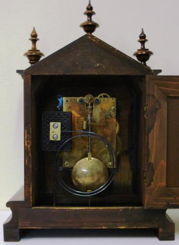 Fruit wood and pine cased 8 day bracket clock circa 1900. Dome topped case with turned finials and side columns on a solid plinth base. Front opening casework with flat glass over steel dial plate with applied gilt spandrels and gilt winged angel head decoration. Silvered chapter ring with matt gilt brass centre and black roman hours with decorative blued steel hands. Square brass gong striking, spring driven, pendulum regulated movement, maker unknown but numbered to the back plate #82449