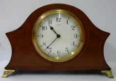 "French 8 day mantel clock timepiece circa 1920 by Bayard, with boxwood inlay and marquetry panels on gilt brass bracket feet. Gilt brass bezel with convex glass over white enamel dial with black arabic hours and blued steel hands. Brass drum movement numbered #12889 with the Bayard back stamp, and inscribed '8 Days, Lever Movement, Made in France', '2 Jewels'.  Dimensions: Height - 6"", width - 8.5"", depth - 3""."