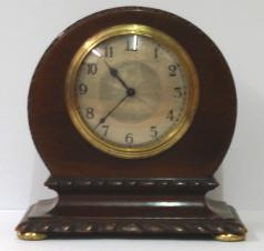 "French 8 day mantel timepiece circa 1920 with round top dark mahogany case with carved plinth decoration and gilt bun feet. Gilt brass bezel with convex glass over a silvered dial with engine turned centre and black arabic hours and black steel hands. Brass drum movement with contemporary cylinder escapement platform, and stamped 'Made in France' with a captive winding key.  Dimensions: Height - 7"", width - 6.5"", depth - 3.75""."