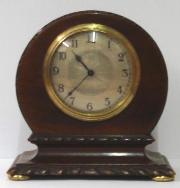 French 8 day mantel timepiece circa 1920 with round top dark mahogany case with carved plinth decoration and gilt bun feet. Gilt brass bezel with convex glass over a silvered dial with engine turned centre and black arabic hours and black steel hands. Brass drum movement with contemporary cylinder escapement platform, and stamped 'Made in France' with a captive winding key.