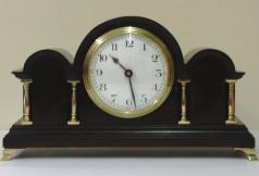 "French 8 day mantel clock timepiece in an impressive triple arched dark mahogany case with gilt brass columns and bracket feet. Gilt brass bezel with convex glass over a white enamel dial with black arabic hours and black steel hands. Brass drum case movement maker unknown stamped 'France' with a good quality replacement lever escapement platform and a captive winding key.  Dimensions: Height - 11"", width - 6"", depth - 3.5""."