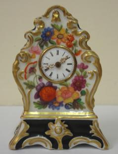"Good quality porcelain cased bedside or mantel clock with applied gilding and enamel flower decoration throughout. White enamel dial with slight damage, black roman hours and ornate gilt metal hands. Miniature brass spring driven late 19th century 8 day movement, maker unknown, with gilt pendulum.  Dimensions: Height - 3.5"", width - 2.25"", depth - 1.5""."