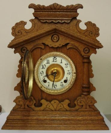 American 8 day oak cased 'Vernon' mantel clock circa 1890, by the Ansonia Clock Co. Highly carved and decorated case with half turned pillars and applied mouldings. Gilt brass bezel with flat chamfered glass over ivorine chapter ring with gilt brass centre. Black gothic hours and ornate black steel hands and slow / fast adjuster at 12 o'clock. Spring driven, gong striking skeletonised brass movement with original pendulum, and stamped 'Ansonia Clock Co.' and 'Patented - June 18, 1882'.