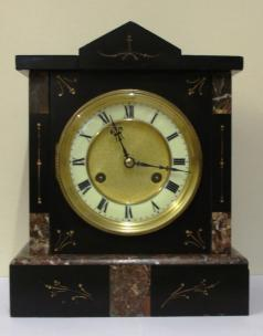 "German 8 day slate and marble cased mantel clock circa 1900 by Jungans. Architectural square case with decorative engraved decoration with gilt infill. Gilt circular bezel with flat chamfered glass and white enamel chapter ring with a matt gilt interior together with black roman hours and ornate blued steel hands. Good quality spring driven, gong striking movement, regulated by a pendulum and with the Junguns touch mark.  Dimensions: Height - 11.5"", width - 9.5"", depth - 5.5""."