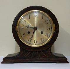 "8 day dark stained oak and pine cased mantel clock circa 1920. Balloon shaped case with applied decorative moulding. Circular gilt bezel with convex glass, silvered dial with black arabic hours and black steel hands and strike / silent selection at 3 o/c. Square brass pendulum regulated, spring driven, gong striking movement, maker unknown.  Dimensions: Height - 9.5"", width - 11"", depth - 6""."