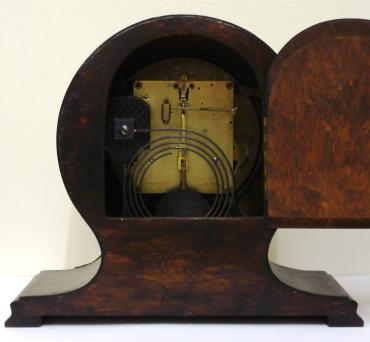 8 day dark stained oak and pine cased mantel clock circa 1920. Balloon shaped case with applied decorative moulding. Circular gilt bezel with convex glass, silvered dial with black arabic hours and black steel hands and strike / silent selection at 3 o/c. Square brass pendulum regulated, spring driven, gong striking movement, maker unknown.