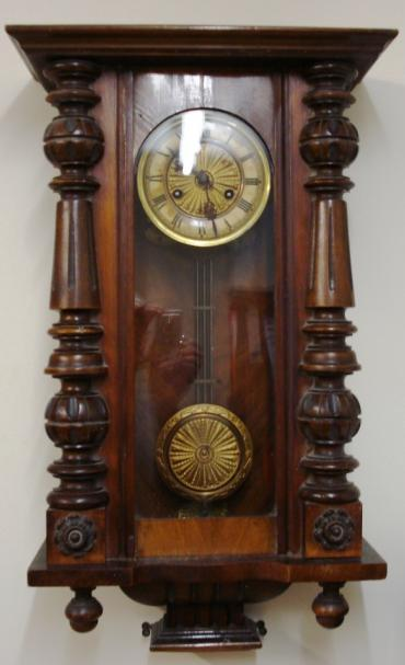 Clock for sale for restoration:- Vienna Regulator style walnut and pine cased gong striking wall clock by Kienzle. Flat top pediment full length door with fluted and turned side columns, original glass over ivory coloured dial with black roman hours and ornate blued steel hands. Standard brass spring driven pendulum regulated 8 day movement circa 1890 with faux gridiron and sunburst pendulum boss. Back plate has the Kienzle touch mark and is stamped D.R.Patent. Lacks original crest and finials and has discolouration to dial and pendulum suspension spring is broken.