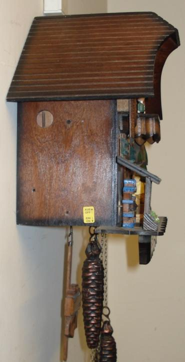 Modern German Automaton musical box day going cuckoo clock. Carved pine wood case with pine tree, water wheel and woodsman decoration. Traditional carved light coloured wood chapter ring with roman hours and matching wooden hands. Visible pendulum and triple cast metal pine cone weights. On the hour the carved wood cuckoo bird displays the hours, and the mechanism activates the figure carousel, the woodman chopping and the water wheel turning.
