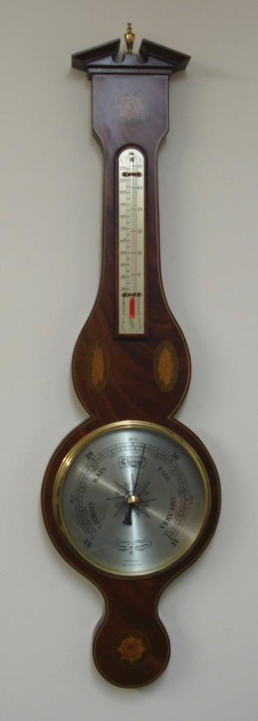 Modern Comitti of London compensated barometer in a wood veneer case with marquetry inlay. Circular gilt brass bezel over a silvered dial with black painted index and a separate alcohol Centigrade and Fahrenheit thermometer.