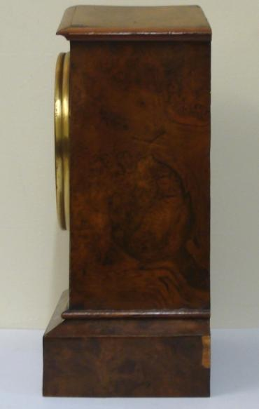 American 8 day burr walnut veneer cased mantel clock timepiece circa 1900. Simple arch topped case with integral plinth. Gilt brass bezel with flat glass over a silvered dial with black arabic hours and black steel moon hands. Simple brass, spring driven pendulum regulated, movement which because of the solid casework construction, only accessible from under the clock.