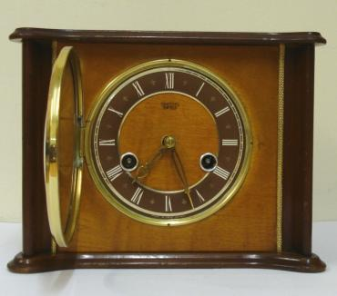 English Smiths Enfield 8 day wood veneer cased gong strike mantel clock circa 1950. Unusually shaped flat top case with gilt bezel and domed glass over a dark brown chapter ring with white roman hours and pierced gilt hands. Rear door to brass spring driven, floating balance movement with slow / fast regulation. Time adjust and winding squares behind the front face glass.