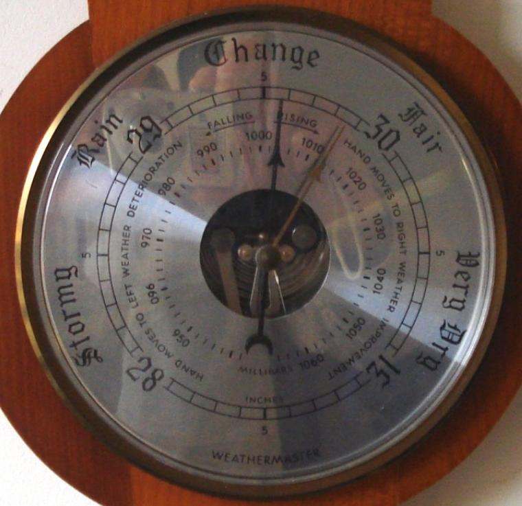 Modern Weathermaster aneroid barometer in a wood veneer case with brass finial. Circular gilt brass bezel over a silvered dial with black painted dual pressure index and a visible action. Separate alcohol Centigrade and Fahrenheit thermometer.