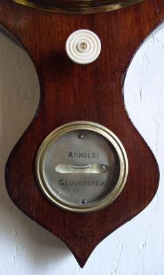 Arnoldi of Gloucester, oak cased mercury barometer with onion style top and bottom, and silvered dials: - hygrometer, thermometer, convex mirror, barometer, an ivory hand adjuster, and bubble level gauge.
