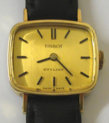 Ladies Tissot Stylist gold plated cased manual wind wrist watch on a black leather strap with gilt buckle. Matt gilt dial with black baton hour markers and matching black hands. Swiss signed Tissot 17 jewel movement numbered #12738037 with stainless steel  case back numbered 19182 - 03.