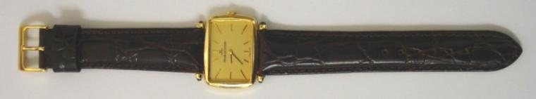 Swiss Jaegar LeCoultre manual wind wrist watch in a 18ct gold case on a brown leather strap with gilt buckle. Gold coloured dial with gilt baton hour markers and black and gilt hands. Signed jewelled lever movement with case numbered #4459 21 and #1350038 with London import hallmark for 1972.