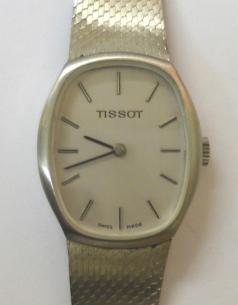 Tissot manual wind wrist watch housed in a stainless steel case with integral stainless steel adjustable bracelet. Brushed silver dial with polished silver and black hour markers and matching black hands. Signed Tissot calibre 2180 jewel lever incabloc movement numbered #21141 with signed case back numbered #10933.