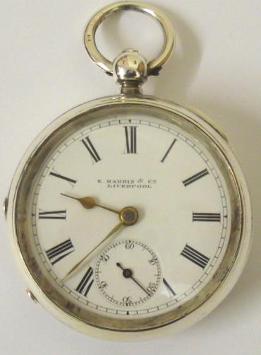 English lever silver cased pocket watch by E.Harris of Liverpool with Birmingham hallmark for 1892. Key wind and time change, white enamel dial with black Roman hours and gilt spear and shaft hands. Engraved back plate signed and numbered #226332 with engraved cock piece and jewelled end stone.