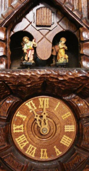 New 3 weight driven 8 day duration cuckoo clock with cuckoo displaying on the hour and half hour and striking on a gong. Decorative carved case with castle themed building, and vine leaf pendulum. The clock features an automaton of dancing figures, and a two tune musical movement.