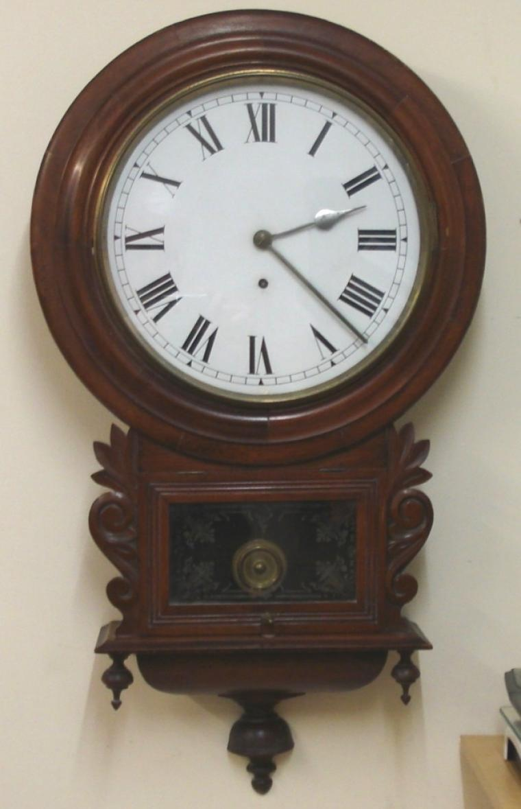 "English 8 day wall clock by the British United Clock Co. Ltd of Birmingham. Round mahogany case with brass bezel and flat glass over a white painted dial with black Roman hours and polished silvered hands. Lower extended drop dial with carved and moulded casework and visible pendulum window. Signed basic brass spring driven, pendulum regulated, time piece movement, circa 1900.  Dimensions: Height - 30"", Width - 10.5"", Depth 5""."