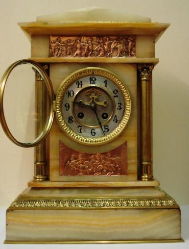 French 8 day gong striking, marble cased clock garniture, with Brocot style visible escapement. The movement by L.Marti et Cie with a 'Medaille de Bronze' backstamp is numbered 48 and is circa 1890. It is housed in an architectural style two colour marble case and is accompanied by two marble and brass side pieces surmounted by gilded urns. All three pieces display greek neo clcassical copper plaques and ornate gilded brass fluted columns with acanthus leaf plinths.