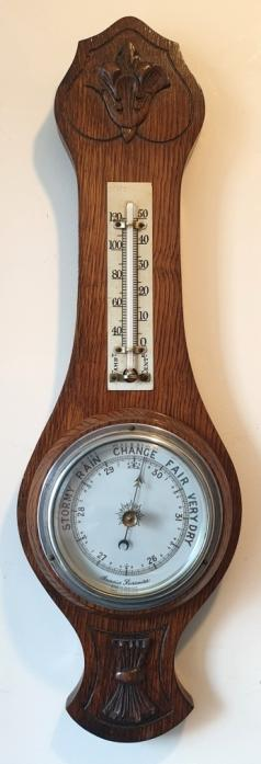 English carved dark oak mounted aneroid barometer and thermometer, circa 1930s. Circular silvered brass bezel with chamfered flat glass over a white dial with black inches of mercury pressure index and a blued steel pressure indicating hand with a gilt history marker hand together with a mercury thermometer displaying temperature in both Fahrenheit and Centigrade.